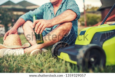 Gardening. Senior man take a rest in the yard and enjoying in beer after work with a lawn mower. Hobbies and leisure #1359329057
