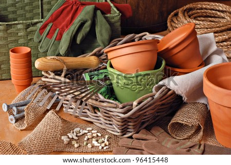 Gardening still life with flower pots, gardening tools, and planting supplies in wicker baskets with burlap and rope.