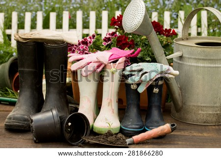 gardening tools, adult and child boots and handshoes in the garden