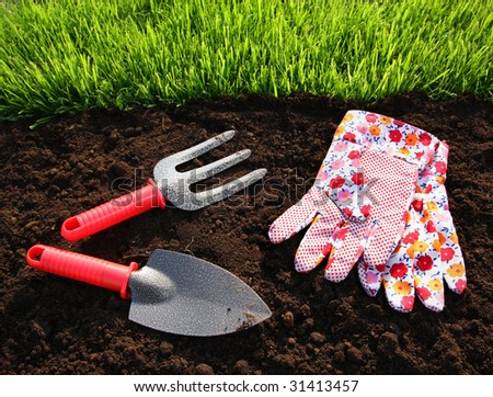 Gardening tools, fresh grass and soil