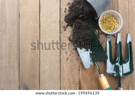 gardening tools on wooden plank background