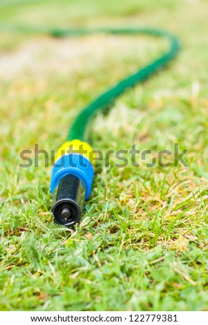 Gardening water pipe lying and dripping a drops of water to dry ground druing hot summer