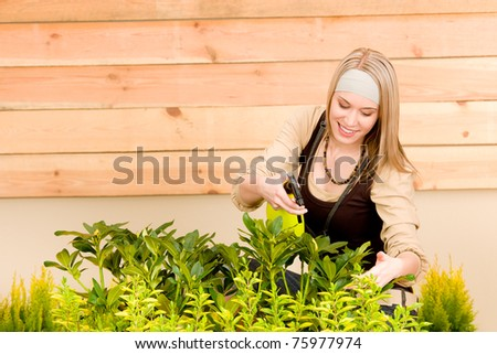 Gardening woman watering plants in spring on terrace