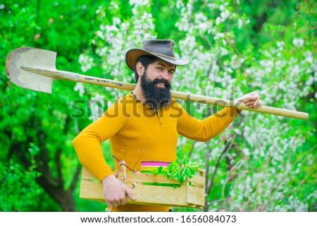 Gardening. Work in garden. Bearded man with gardening tools. Work in garden. Gardener work. Farm. Spring. Smiling man preparing to planting. Plants. Garden spade.