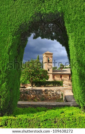 Gardens of La Alhambra with Convent of San Francisco in the background in Granada, Spain