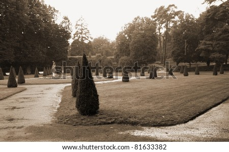 Gardens of the palace in Rogalin (Poland), on a rainy day, in sepia