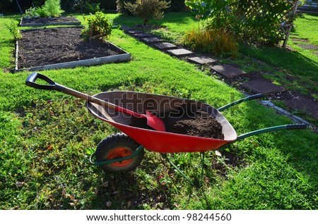 Gardner has a tea break overlooking his wheelbarrow and garden. - stock photo