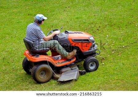 Gardner on ride-on lawn mower cutting grass. #216863215