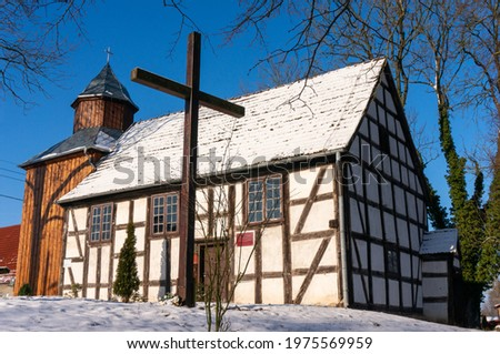 Gardno, Poland - January 17 2021: Half-timbered church Saint Matthew the Apostle dates from 1737 (Kościół św. Mateusza Apostoła). Wooden cross in front of the temple, the roof is covered with snow. Zdjęcia stock ©