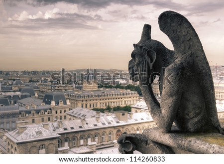 Gargoyle (chimera) on Notre Dame de Paris close up against a moody sky, HDR