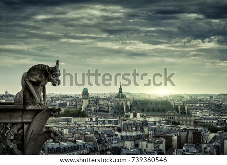 Gargoyle (chimera) on the Cathedral of Notre Dame de Paris overlooking Paris at night, France. Paris skyline in twilight. Aerial mystic view of Paris with gargoyle at sunset. Panorama of city at dusk.
