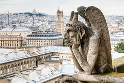 Gargoyle (chimera) on the Notre Dame de Paris cathedral overlooking Paris, France. Notre Dame is one of the main architecture landmarks in Paris. View of Paris from above with demon statue close-up.
