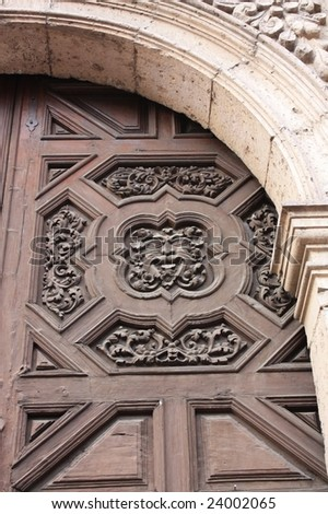 Gargoyle face on ancient carved wood door; Morelia, Mexico