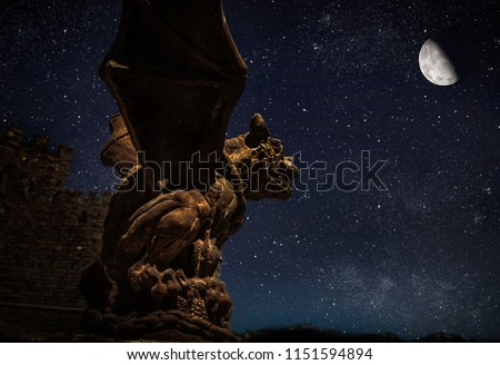 gargoyle statue against moon lit night sky