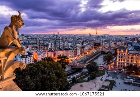 Gargoyle statue on edge of Notre-Dame cathedral with view of illuminated Paris city in cloudy twilight #1067175521