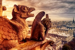 Gargoyles or chimeras on Notre Dame de Paris overlooking Paris, France. Old cathedral of Notre Dame is a famous landmark of Paris. Dramatic view of Paris with the vintage demon statues on fire.