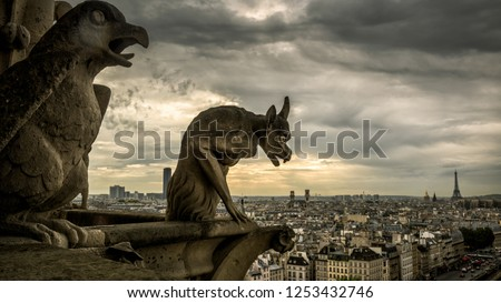 Gargoyles or chimeras on the Cathedral of Notre Dame de Paris overlooking Paris, France. Gargoyles are the famous Gothic landmarks in Paris. Dramatic skyline of Paris with the vintage demon statues.
