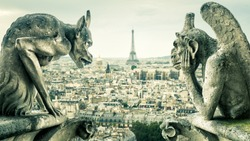 Gargoyles or chimeras on the Notre Dame de Paris overlooking Paris city, France. Old cathedral of Notre Dame is a famous landmark of Paris. Dramatic view of Paris with the vintage demon statues.