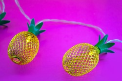 garland lights, shape of pineapple on pink background