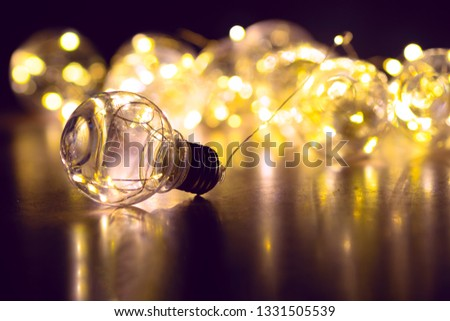 Garland of light bulbs on a black background. Place for text. #1331505539