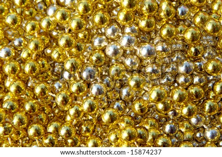 Garland of shiny gold lays in a bright cluster of gold.