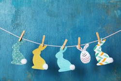 Garland with handmade Easter bunnies on wooden background
