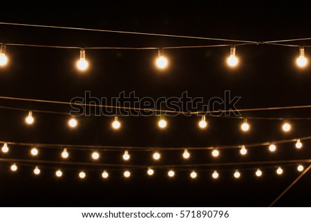 Garlands of lamps on a wooden stand on the street. A wedding Banquet. #571890796