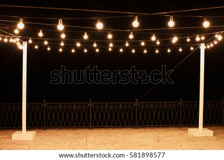 Garlands of lamps on a wooden stand on the street. A wedding Banquet.