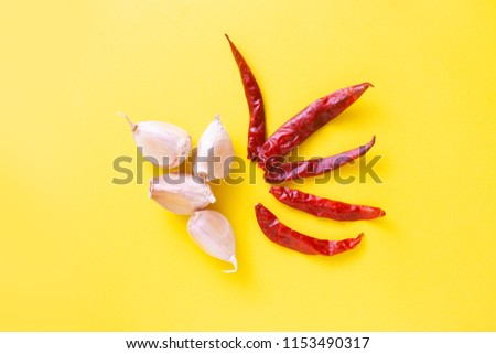 garlic and chilies on yellow background #1153490317