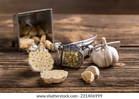 Garlic and garlic press on rustic wooden board