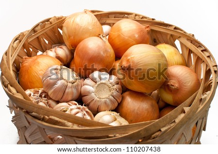 Garlic and onion bulbs in bamboo basket isolated on white background