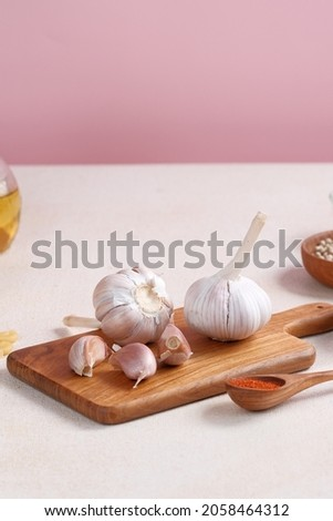 Garlic bulb on wooden chopping board. Cooking preparation concept. Selective focus, copy space.