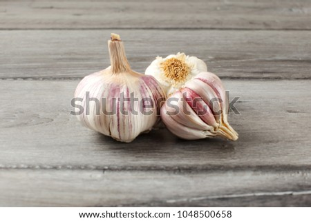 Garlic bulbs, purple cloves under cracked skin on gray wood table.