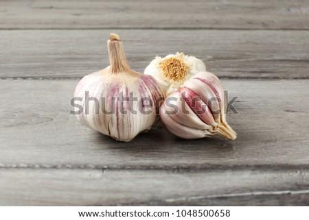 Garlic bulbs, purple cloves under cracked skin on gray wood table.