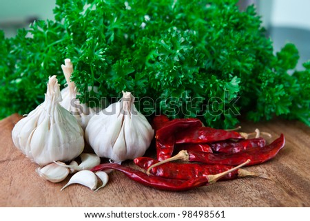 Garlic, chilli, parsley on wooden cutting board