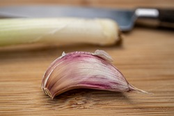 Garlic clove  (Allium sativum) with spring onion and knife on a kitchen board