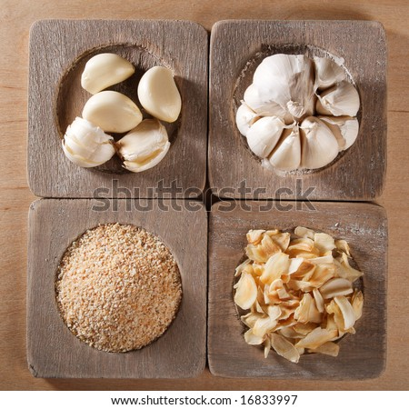 garlic cloves, bulb, flakes and powder on old wooden plates