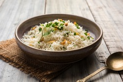 Garlic Fried Rice Or Pulav using Basmati Rice and Lahsun, served with Dal Tadka over moody background, selective focus