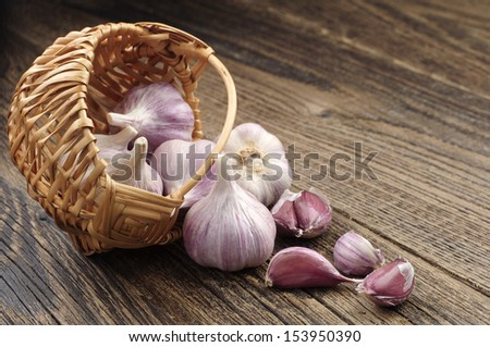 Garlic in a wicker basket and near on wooden table