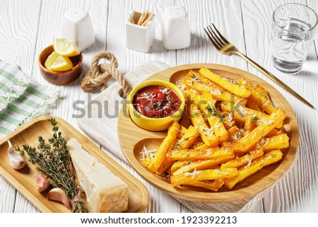 garlic parmesan polenta fries with parmesan cheese, thyme and spices in a bamboo dish with tomato sauce on a white wooden table, italy cuisine
