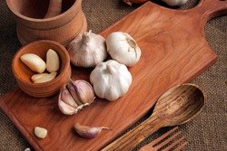 Garlic. sliced garlic, garlic clove, garlic bulb in wooden bowl place on chopping block on vintage wooden background. Place for text,  copy space Concept of healthy food. Top view