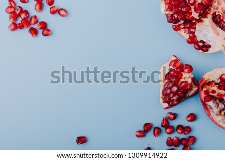 Garnet background. Ripe red garnet fruit. Garnet fruit slices on a blue background. Vegetarian Concept, Organic Vitamins. Flat lay, top view. Place for text, copy space.  #1309914922