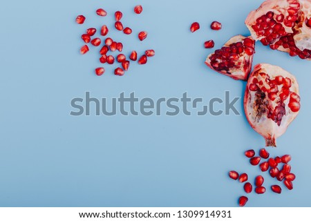 Garnet background. Ripe red garnet fruit. Garnet fruit slices on a blue background. Vegetarian Concept, Organic Vitamins. Flat lay, top view. Place for text, copy space. Abstract colorful background.  #1309914931