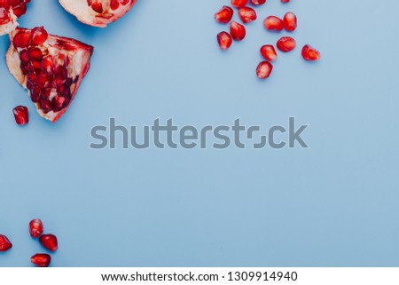 Garnet background. Ripe red garnet fruit. Garnet fruit slices on a blue background. Vegetarian Concept, Organic Vitamins. Flat lay, top view. Place for text, copy space. Abstract colorful background.  #1309914940