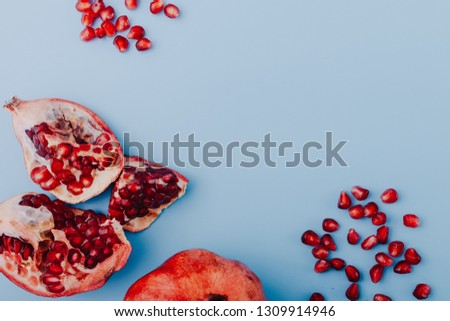 Garnet background. Ripe red garnet fruit. Garnet fruit slices on a blue background. Vegetarian Concept, Organic Vitamins. Flat lay, top view. Place for text, copy space. Abstract colorful background.  #1309914946