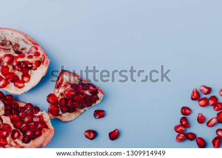 Garnet background. Ripe red garnet fruit. Garnet fruit slices on a blue background. Vegetarian Concept, Organic Vitamins. Flat lay, top view. Place for text, copy space. Abstract colorful background.  #1309914949