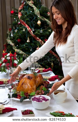 Garnished Christmas roasted turkey in young beautiful woman hands prepared for traditional family dinner with salad, fruits, vegetables, wine and champagne glasses on Christmas tree background