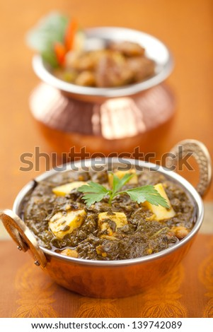 Garnished Palak Paneer in a copper bowl.