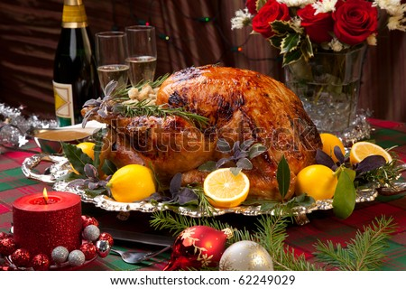 Garnished roast turkey on Christmas-decorated table with candles and flutes of champagne