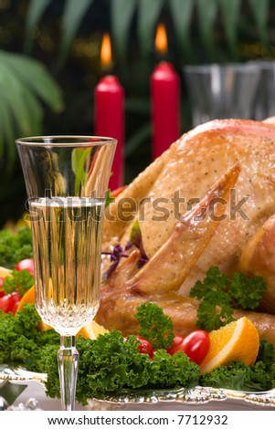 Garnished roasted turkey on Christmas decorated table with candles and flutes of champagne. Shallow DOF. Focus on glass.